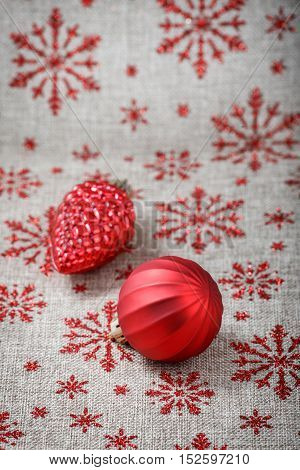 Red Christmas ornaments on canvas background with red glitter snowflakes. Xmas card. Happy New Year. Space for text