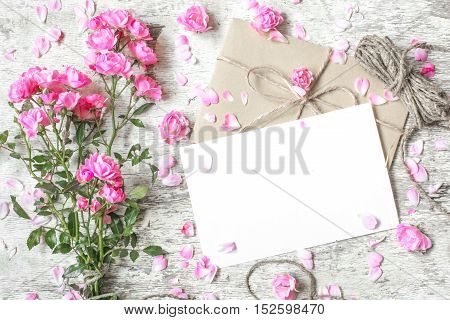 blank white greeting card with pink roses bouquet buds with petals around and vintage rope with copy space