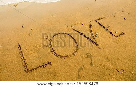 The inscription Love on the yellow sand. Beach sand writing. Romantic seaside photo background or card template. Love word on seashore surface with bare foot marks. Empty beach and waterline