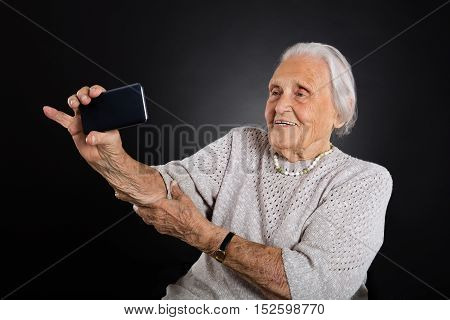 Portrait Of Smiling Elder Woman Taking Selfie Using Smartphone Over Grey Background