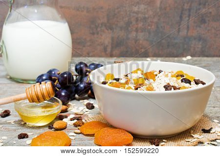bowl of oat muesli with fruits berries honey and nuts and milk jug on background. healthy breakfast