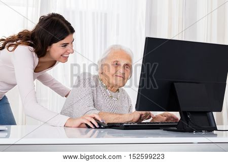 Young Woman Helping Her Grandmother For Using A Laptop On Desk At Home