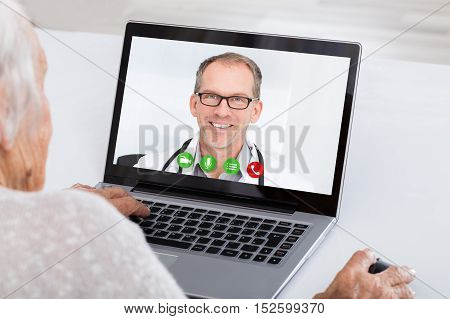 Close-up Of Senior Woman Video Conferencing With Doctor On Laptop At Home