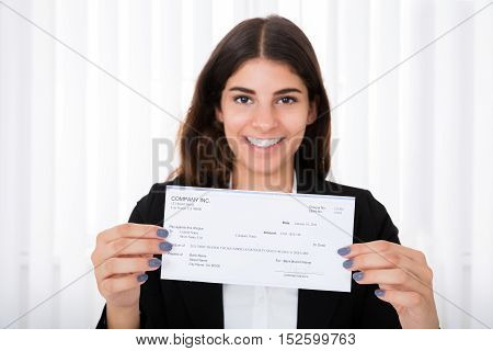 Successful Businesswoman Showing Cheque On Desk In Office