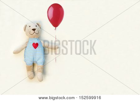 Teddy bear with red balloon on a white background