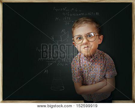 Emotional pupil boy near the chalkboard with formulas