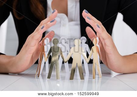 Close-up Of Businesswoman Hand Protecting Cut-out Figures On Desk In Office