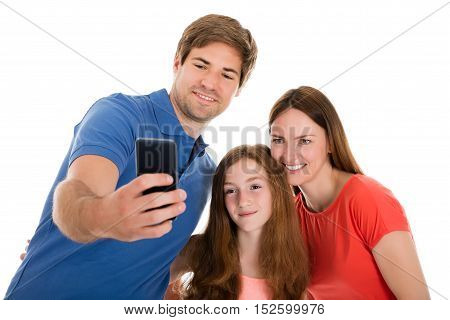 Smiling Young Parent Taking Selfie With Their Daughter On Cellphone