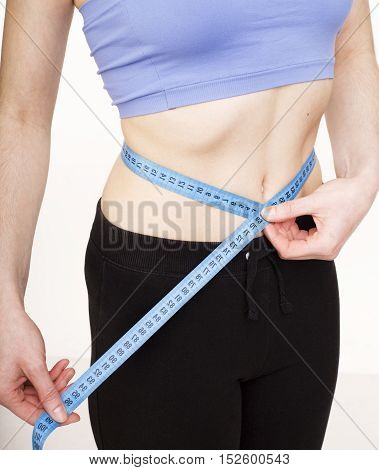 girls stomach measuring with tape isolated on white background, skiny woman on diet, healthcare people concept close up