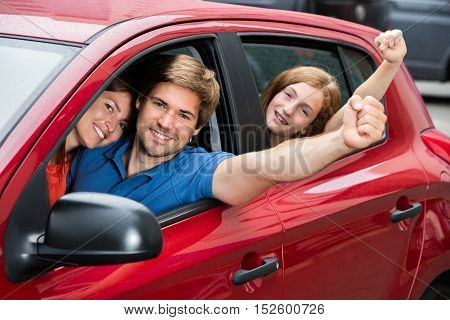 Happy Family Sitting In Newly Purchased Car Raising Their Arms