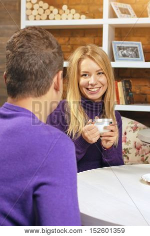 Young girl looks at the guy and drinking coffee. The first meeting shyly smiling and carrying on a conversation.