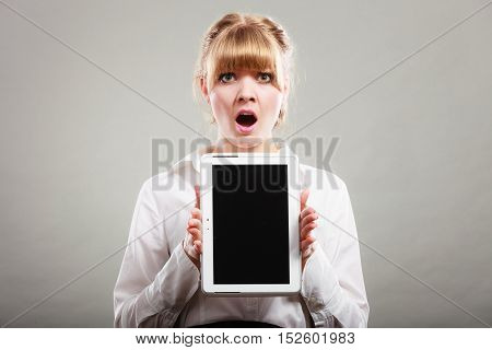 Amazed shocked elegant businesswoman holding blank screen showing copy space. Woman advertising new modern technology.