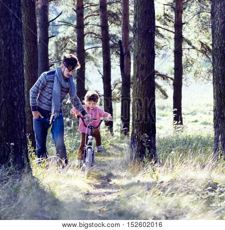 father learning his son to ride on bicycle outside in green park, real happy family, lifestyle people concept close up