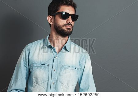 Young hipster bearded man with sunglasses - gray background
