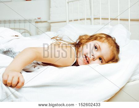 portrait of little cute real girl in bed at home close up, lifestyle happy smiling people concept