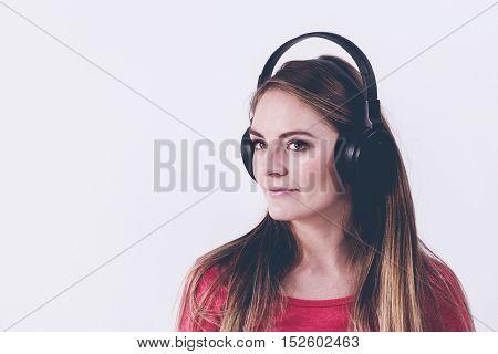 Charming woman listen to music. Female keep headphones.