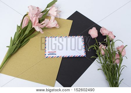 Composition with envelope and flowers. On envelope - the inscription Air Mail in English French and Spanish. Photo background with white and black paper. Natural backdrop for wedding invitation
