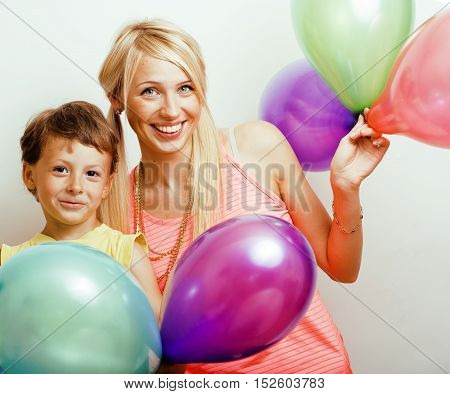 pretty real family with color balloons on white background, blonde mother with cute son on birthday party celebration, lifestyle people concept close up