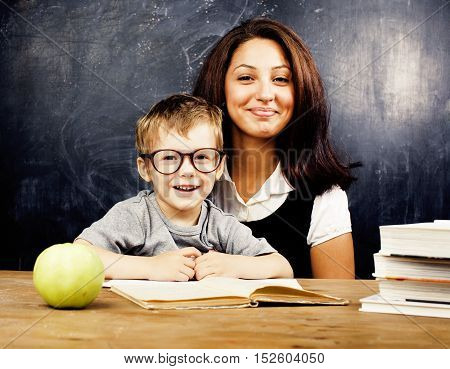 little cute boy with young teacher in classroom studying at blackboard smiling, lifestyle people concept close up