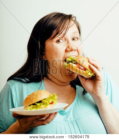 fat white woman having choice between hamburger and salad, eating emotional unhealthy food, lifestyle people concept close up