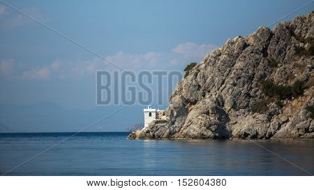 Lighthouse on a cliff in the Aegean sea.