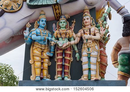 Madurai India - October 21 2013: Under the belly of a horse is the wedding between Meenakshi and Shiva reenacted with the help of Vishnu. All colorful statues at Karuppana Sami shrine near Nagamalai.