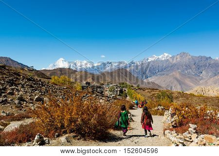 People descending down a dirt path to Muktinath. Sacred place for Hindus and Buddhists.