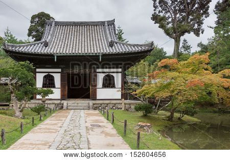 Kyoto Japan - September 19 2016: Smaller hall of the Kodai-ji Buddhist Temple complex sits in a beautiful garden which starts to show autumn colors. Gray sky.