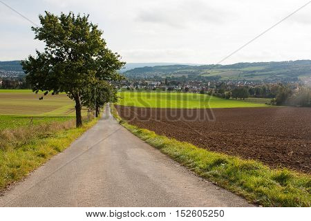 A landscape with agricultural fields a road trees and hills and a small town on the background. Location Bad Pyrmont North Germany.
