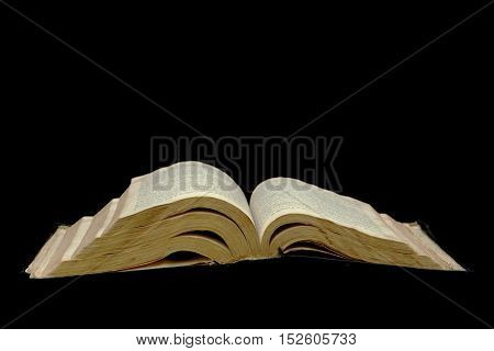Open Bible isolated on a black background