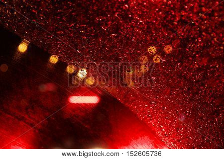 Raindrops on the windshield of the car lit night lights.