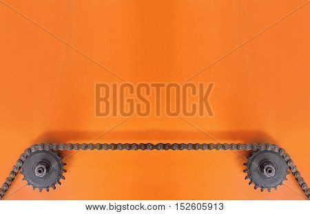 Black metal cogwheels and chain on orange background with empty space for text.