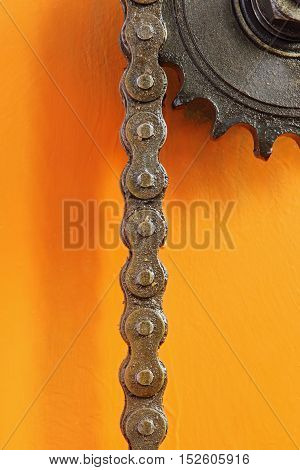 Black metal cogwheel and chain on orange background taken closeup.