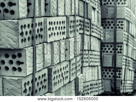 Lot of stacks of clay bricks with holes black and white colors