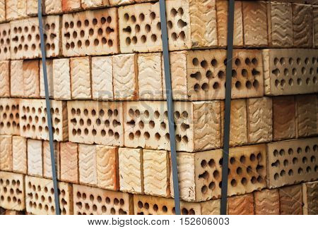 Lot of stacks of red clay bricks with holes