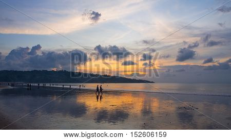 Holiday makers at Jimbaran Beach in Bali Indonesia at sunset.