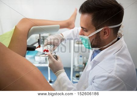 Young  Gynecologist Putting Gel On Equipment To Exam Patient