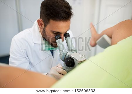 Young Professional Gynecologist Exam Patient With Colposcope