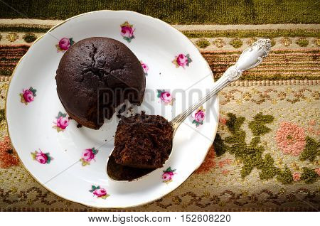 Chocolate fondant, souffle cake with whipped cream on decorative plate, top view