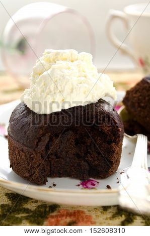 Chocolate fondant, souffle cake with whipped cream on decorative plate.