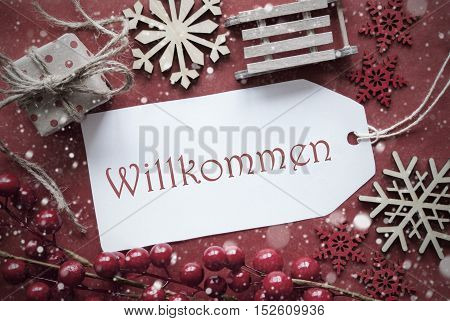 Nostalgic Christmas Decoration Like Gift Or Present, Sleigh. Card For Seasons Greetings With Red Paper Background. German Text Willkommen Means Welcome