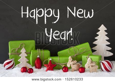 English Text Happy New Year. Green Gifts Or Presents With Christmas Decoration Like Tree, Moose Or Red Christmas Tree Ball. Black Cement Wall As Background With Snow.