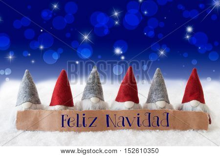 Label With Spanish Text Feliz Navidad Means Merry Christmas. Christmas Greeting Card With Gnomes. Sparkling Bokeh And Blue Background With Snow And Stars.