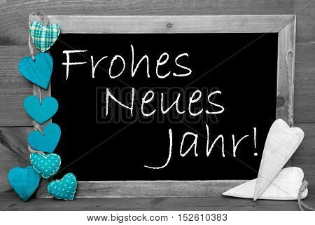 Chalkboard With German Text Frohes Neues Jahr Means Happy New Year. Turquoise Hearts. Wooden Background With Vintage, Rustic Or Retro Style. Black And White Image With Colored Hot Spots.