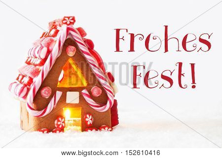 Gingerbread House In Snowy Scenery As Christmas Decoration With White Background. Candlelight For Romantic Atmosphere. German Text Frohes Fest Means Merry Christmas