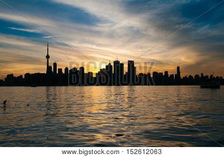 View of Toronto skyline silhouette at sunset over Ontario lake