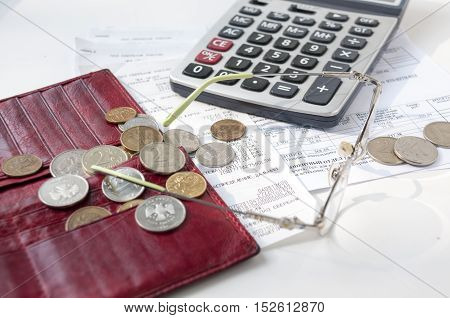 Near empty purse are checks and receipts calculator and glasses scattered coins