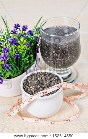 Healthy Chia seeds in white cup and soak in water with measuring tape on tablecloth.