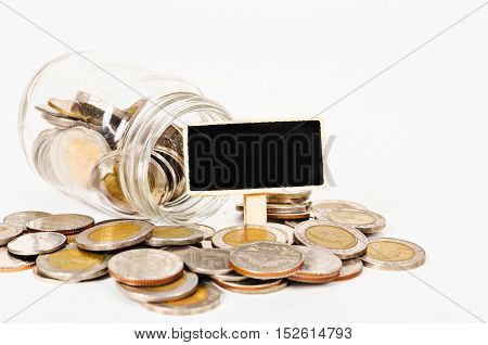Coins in glass money jar with black wooden tag for your text isolated on white background.