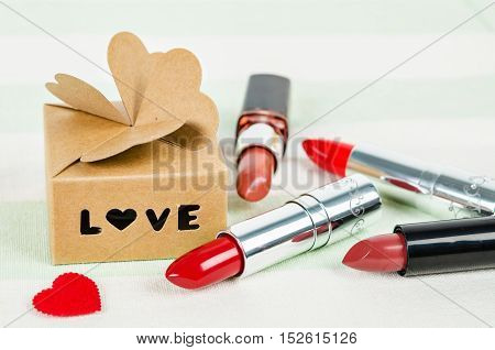 Beautiful luxury red lipstick with love box gift on tablecloth.